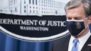 """Liittovaltion poliisin FBI:n johtaja Christopher Wray tiedotustilaisuudessa, jossa kerrotaan syytteistä Kiinan """"operaatio Kettujahtiin"""" liityen. Wrayn kasvoilla on suojamaski."""
