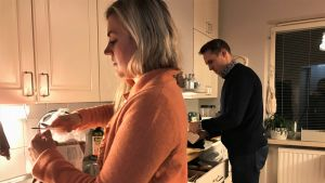 Kvinna och man står i ett kök och gör mat.