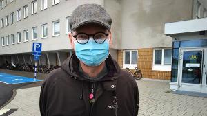 En man med runda svarta glasögon, rutig keps och munskydd står utanför sjukhuset.
