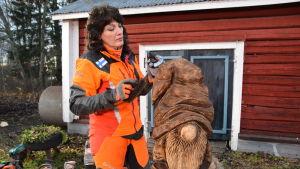 Konstnären Ulla Haglund bränner sin träskulptur-tomte med en blåslamppa.