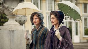 Fru Trenchard och lady Brockenhurst på stadspromenad under varsitt parasoll.