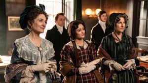 Tre kvinnor står på rad iklädda epokriktiga klänningar.