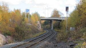 Ett järnvägsspår under en bro och mellan två höga berg.