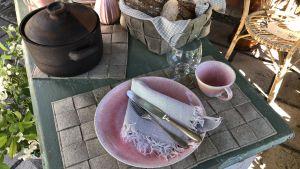 Ett bord är dukat med bordstabletter, grytunderlägg och brödkorg gjorda av linfilt