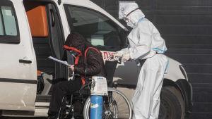 En person i skyddsdräkt, plasthandskar, visir och munskydd hjälper en coronapatient i rullstol in i en bil. Patienten har en syremask med tillhörande syretub.