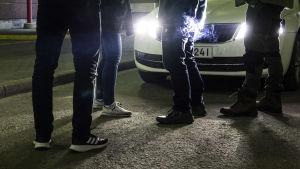 Ihmisten jalkoja auton valojen edessä.