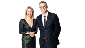 En kvinna i en skinande mörkgrön klänning och en man i mörk kostym och gröna glasögonbågar. De ser glada ut.