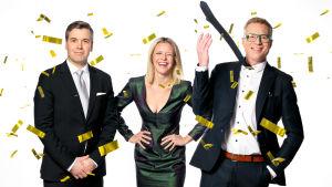 Två män står på båda sidorna av en kvinna. Männen är klädda i kostym, kvinnan i en grön festlig klänning. Det regnar guldfärgad konfetti och alla ser glada ut.