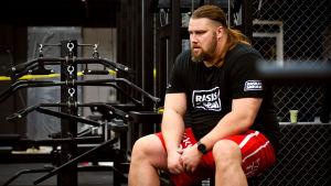 Mika Törrö sitter på bänk i gymet och pustar efter att ha lyft vikter