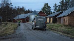 Skoltransporttaxi kommer körande längs landsbygdsväg. En pojke står med sin cykel vid vägrenen och vinkar till taxin.