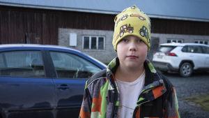 Pojke i gul mössa och färgglad jacka står ute på gård. I bakgrunden står två bilar parkerade.