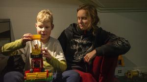 Pojke och hans mamma sitter tillsammans. Pojken roar sig med leksakstraktor.