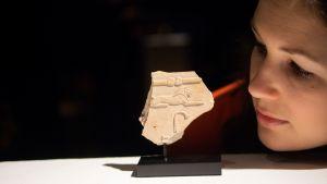 Nainen katsoo museossa näytillä olevaa hieroglyfin palaa.