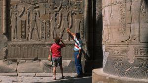 Nainen ja mies tutkivat hieroglyfejä.