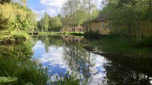 Gamla slitna industribyggnader vid vatten i ett brukssamhälle. Sommar, solsken, grönt gräs och gröna träd. Byggnaderna och den lummiga naturen reflekteras i vattnet.
