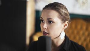 Suvi Tuuli Kataja tyylikkäänä mikrofonin kanssa äänittämässä ohjelmaa Artlabillä. Takana siintää okrankeltainen koristeellinen sohva