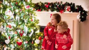 Två barn står glada vid julgranen.