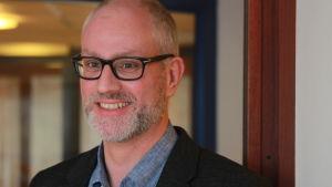 en man i skägg och svarta glasögon med kavaj och ledigt knäppt skjorta