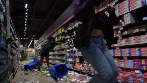 Demonstranter fäller ner produkter i en mataffär på golvet i samband med Black Lives Matter-demonstrationer i Sao Paulo 20.11.2020.