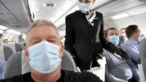 Passagerare och flygvärdinna med munskydd ombord på flygplan.