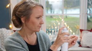 Kvinna håller i flaska med hårspray och sprayar på en miniatyrjulkärve.