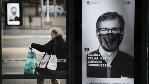En skylt som föreställer en man i munskydd, bredvid sitter en kvinna på en bänk, också hon med munskydd.