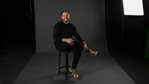 Jonas sitter med benen i kors på en pall i en mörklagd studio.