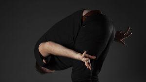 Jonas skakar rumpan, och har huvudet böjt mot marken och armarna utsträckta bakom ryggen, i en mörk studio.