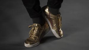 Jonas fötter med guldskor, som försöker göra en balettposé.