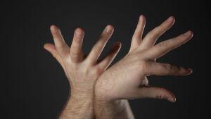 Närbild på två händer som sprätar ut med fingrarna med en mörk bakgrund.