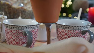 Två koppar håller upp en kruka genom vilken det är tryckt en pinne genom dräneringshålet.
