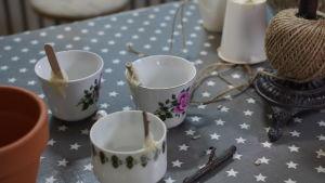 tre kaffekoppar på ett bord. I motsatt sida till örat är det fasttejpade pinnar innuti kopparna.