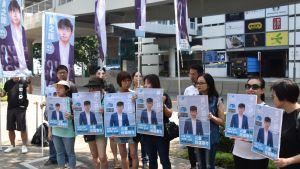 En rad unga står med affischer med Joshua Wongs porträtt.