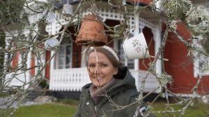 Kvinna står balnd fågelmat som hänger ner från kvistar