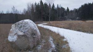 En stor sten invid en gång i åkerlandskap.