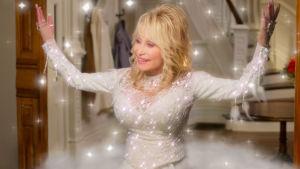 På bilden ses en vitklädd Dolly Parton som spelar en ängel.