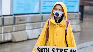 Greta Thunberg skolstrejkar för klimatet i munskydd och gul regnjacka.