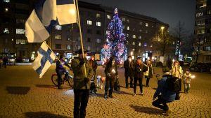 Bild på personer som samlats på torg med finlands flagga.