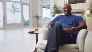 Michael Jordan sitter i en fotölj och skrattar, med ett whiskeyglas bredvid sig.