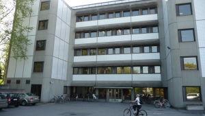 En studerande i vit t-skjorta cyklar fram till studenthälsovårdens hus i Åbo är ett grått höghus i fem våningar.