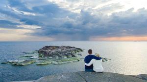 Mies ja nainen istuvat suomalaisessa saaristossa kalliolla ja katsovat auringonlaskua.