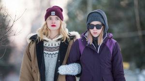 Kaksi nuorta naista (näyttelijät Linda Manelius ja Suvi-Tuuli Teerinkoski) kävelevät talvisessa maisemassa, toisella aurinkolasit.