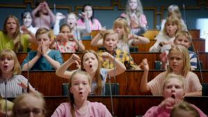 Lapsia eduskuntatalon istuntosalissa.