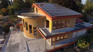 Bild på gult och träfärgat hus med solpaneler på taket.