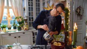 En manlig kock som står i ett kök och häller en sås ur en kastrull över en gryta.
