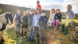 Iso perhe nojailee kiviaitaan Englannin maaseudulla.