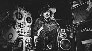Muusikko Sami Yaffa poseeraa kuvitteellisessa äänitysstudiossa. Ahdas tila on pakattu täyteen kelanauhureita, vahvistimia, levyjä ja muuta tavaraa.