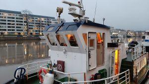 Styrhytten på en blåvit sjöbuss är upplyst en smådimmig morgon i Aura å i Åbo.