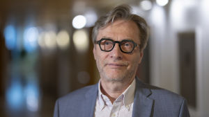 En närbild på ledande överlekare vid Helsingfors och Nylands sjukvårdsdistrikt, Markku Mäkijärvi. Mäkijärvi har glasögon med svarta bågar och en grå kostym på sig.