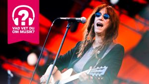 Patti Smith spelar akustisk gitarr och sjunger i en mikrofon.